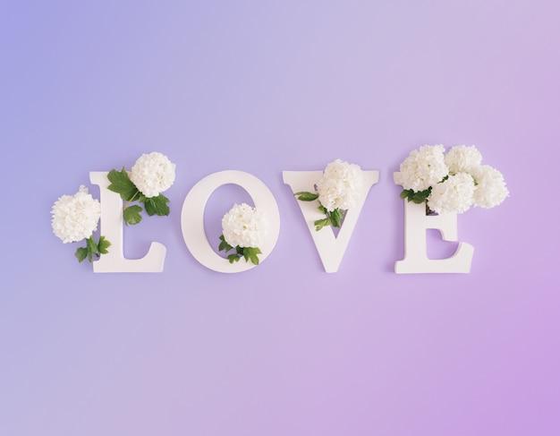 Witte letters op pastelblauwe en paarse gradiëntachtergrond. woord liefde, conceptuele natuur kunst.