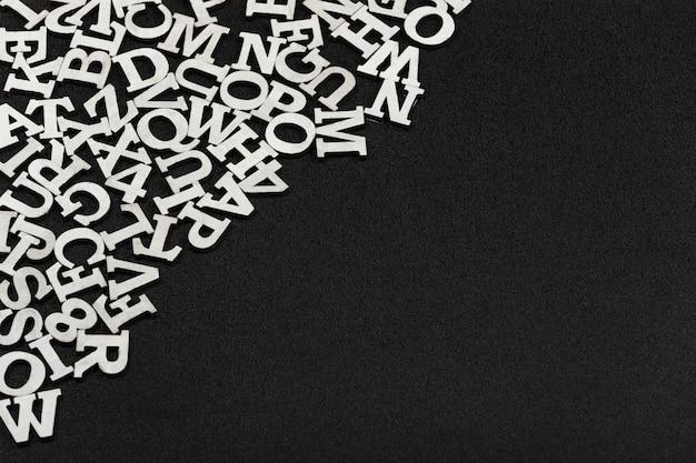 Witte letters van het engels alfabet in willekeurige volgorde op zwarte achtergrond. tekst achtergrond. kopieer ruimte. sjabloon. mockup