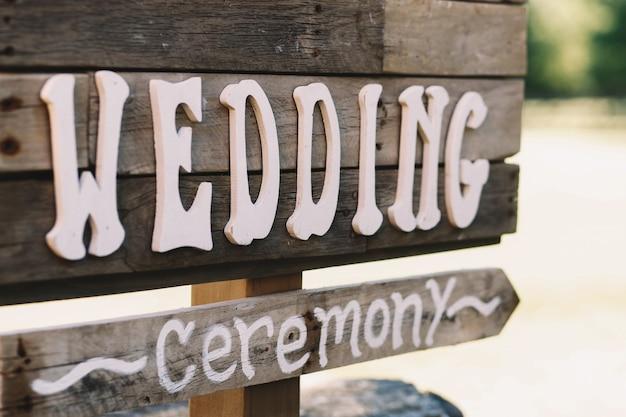 Witte letters 'wedding' op een houten bord