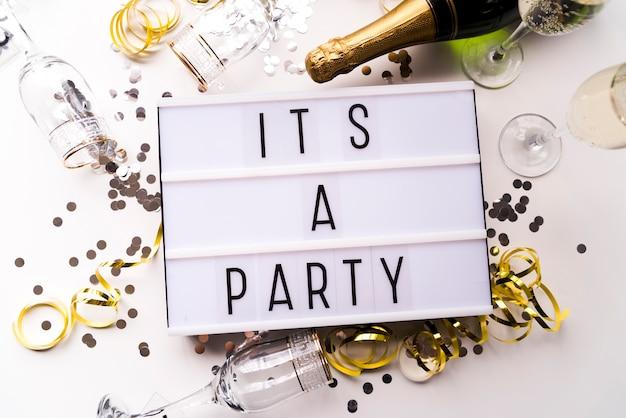 Witte lichtbak met een feesttekst en champagnefles op witte achtergrond