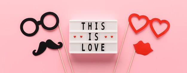 Witte lichtbak met tekst this is love en papieren rekwisieten snor,