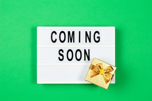 Witte lightbox met tekst die binnenkort komt en kleine gouden huidige doos op groene kleur achtergrond. bovenaanzicht