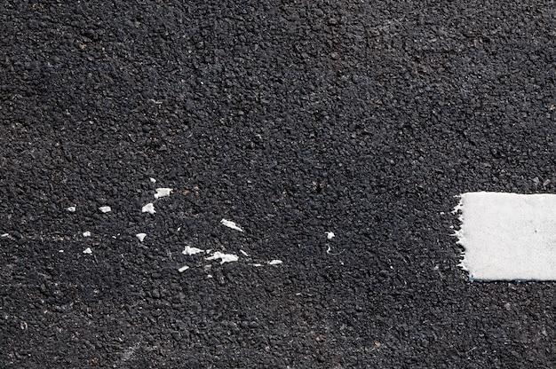 Witte lijn op nieuw asfaltdetail, straat met witte lijntextuur
