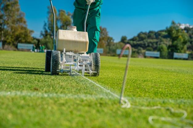 Witte lijnen op het voetbalveld getekend met witte verf op het gras met behulp van een speciale machine voor een wedstrijd