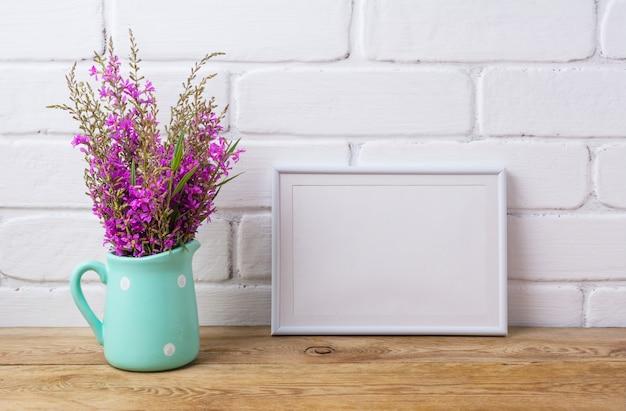 Witte lijst met kastanjebruine paarse bloemen in muntkan