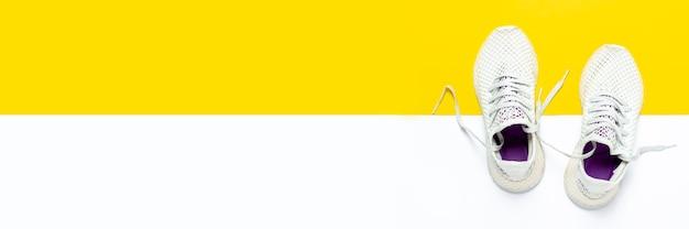 Witte loopschoenen op een abstracte geel-witte ondergrond. concept van hardlopen, training, sport. . plat lag, bovenaanzicht