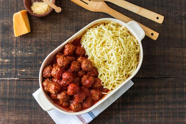 Witte lunchbox gevuld met gehaktballen en trenette pasta