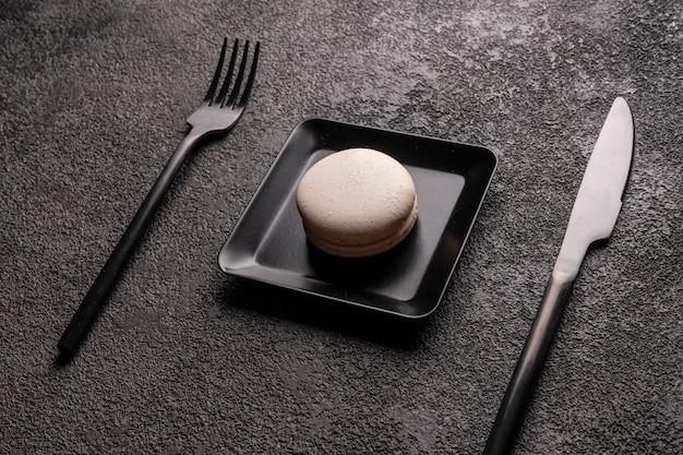 Witte macaron cake in een zwarte vierkante plaat. stijlvol minimalistisch