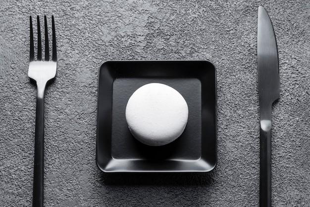 Witte macaroni-cake in een zwarte vierkante plaat. mooie compositie, minimalisme.