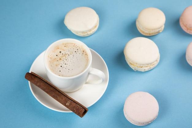 Witte macarons en koffie met kaneel op een blauwe ondergrond