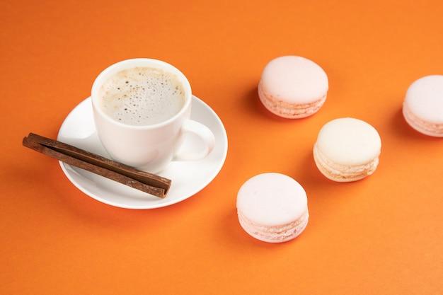 Witte macarons en koffie met kaneel op een oranje ondergrond