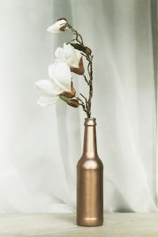 Witte magnolia in een koperen glazen fles