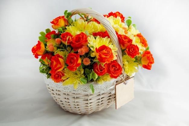 Witte mand met scharlaken rozen en gele chrysanten witte achtergrond voor het snijden van blanco kaarten