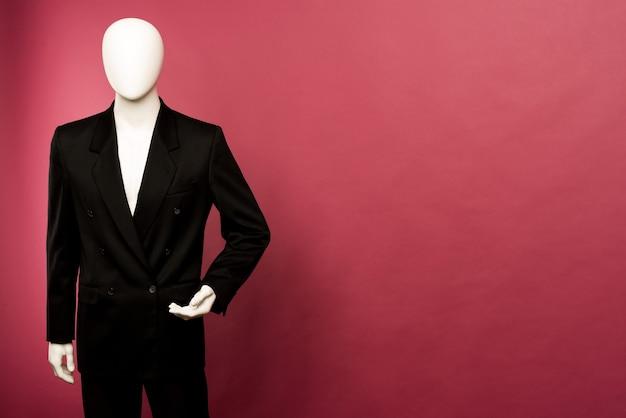 Witte mannelijke etalagepop in een zwart pak op een robijn