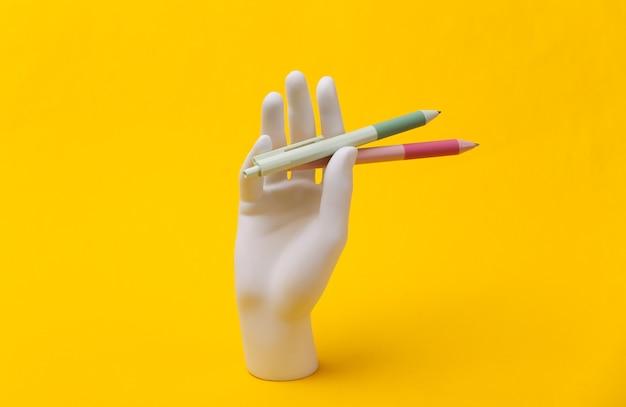 Witte mannequin hand houdt pennen op blauwe achtergrond