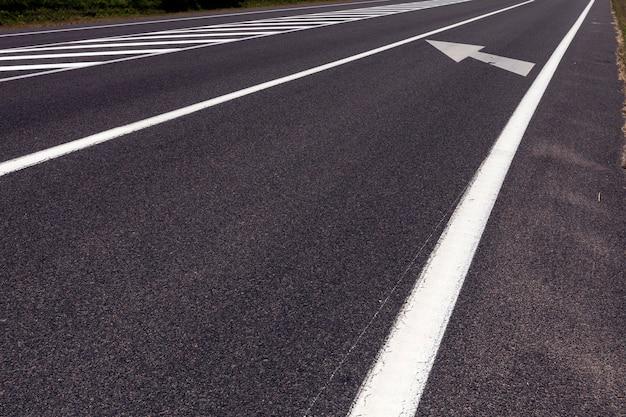 Witte markeringen op de weg om de veiligheid en regulering van het verkeer van auto's te waarborgen, onderdeel van een complex systeem van verkeersregulering dat de veiligheid op de weg garandeert