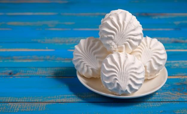 Witte marshmallow op blauwe houten achtergrond