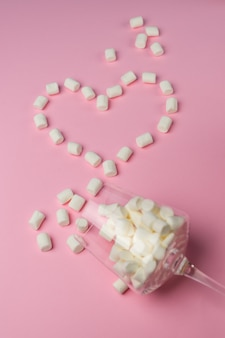 Witte marshmallows aangelegd in een hartvorm op een roze