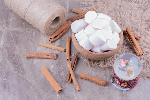 Witte marshmallows in een houten beker met kaneelstokjes rond.
