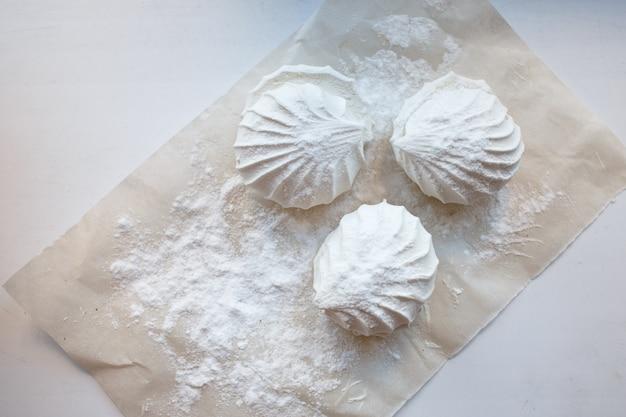 Witte marshmallows op de tafel bestrooid met poedersuiker