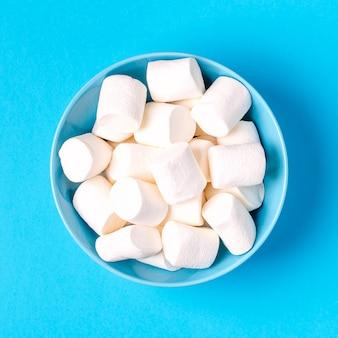 Witte marshmallows voor braden en warme chocolademelk in een kom