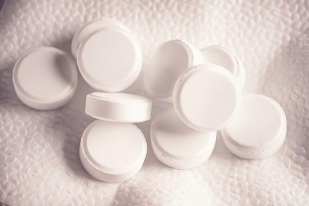Witte medicatiepillen liggen op een witte achtergrond. achtergrondafbeelding over medische en farmaceutische onderwerpen. geneeskunde, farmacie en gezondheidszorg. leven zonder pijn.