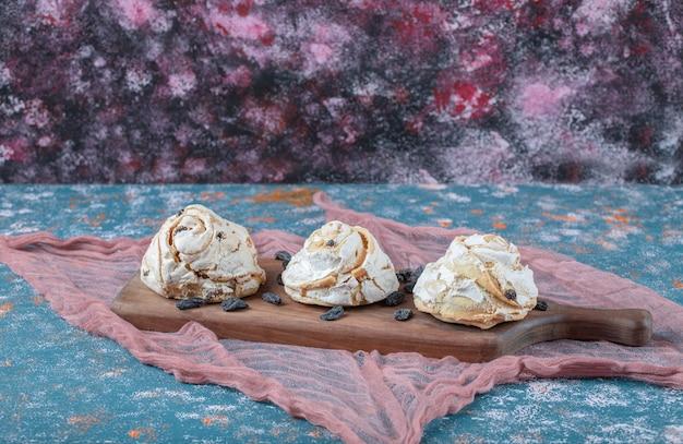 Witte meringue koekjes met zwarte rozijnen op een houten bord.