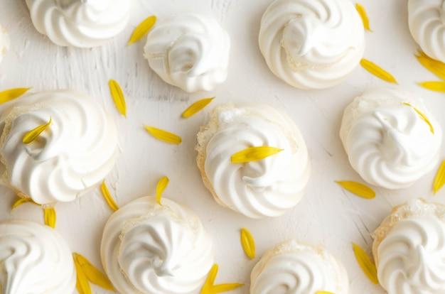 Witte meringuekoekjes met gele bloemblaadjes