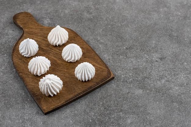 Witte meringuekoekjes op een houten bord