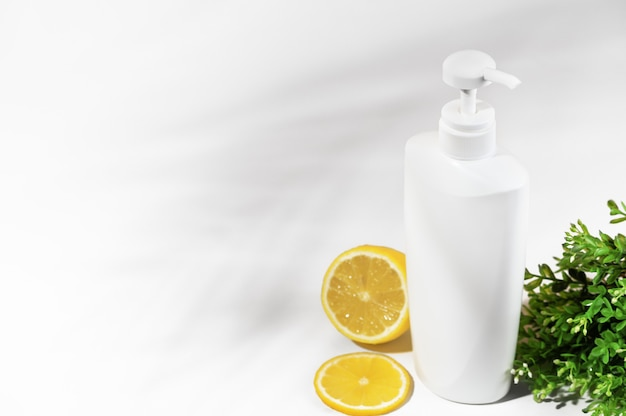 Witte merkloze fles met citroen en groene planten. container met dispenser natuurlijke cosmetische producten. blanco flacon voor lotion, crème, bodylotion, shampoo of haarconditioner. mockup-stijl.