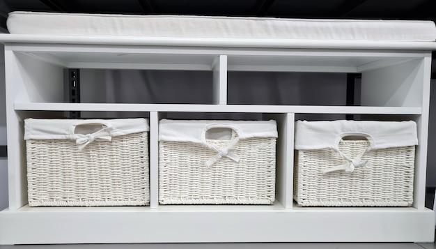 Witte meubels in scandinavische stijl met rieten dozen en poef verkopen in een winkel.