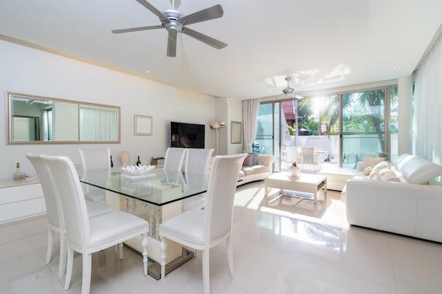 Witte meubels met een bank, een eettafel en een plafondventilator in de woonkamer van villa, huis, huis, appartement en appartement