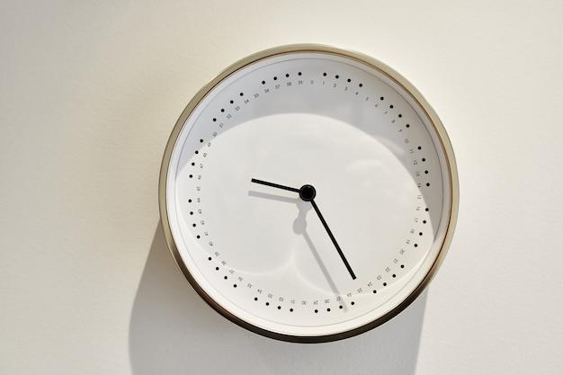 Witte minimalistische klok zonder cijfers aan de muur