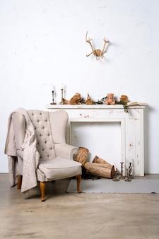 Witte minimalistische loft interieur met open haard, fauteuil en kerstversiering.