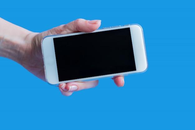 Witte mobiele telefoon in de hand van het linker vrouwtje op blauw met kopie ruimte
