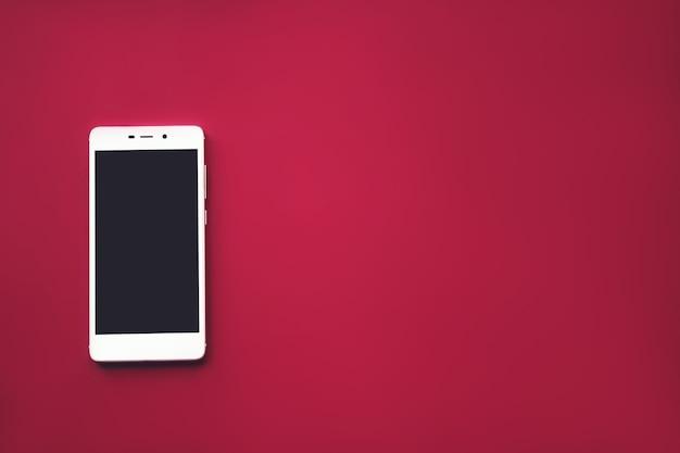 Witte mobiele telefoon op rode achtergrond. digitaal apparaat met zwart scherm. branding mock-up.