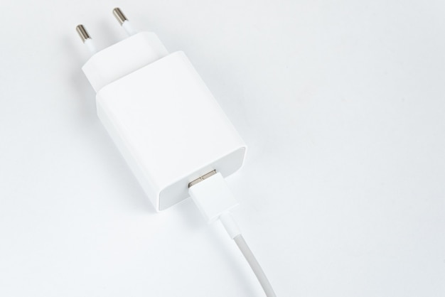 Witte mobiele telefoon oplader op de witte geïsoleerde achtergrond - met usb cabe
