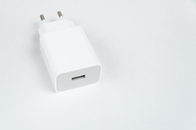 Witte mobiele telefoonoplader op de witte geïsoleerde achtergrond