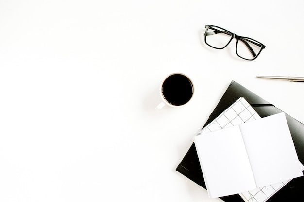 Witte moderne kantoorwerkruimte met lege notebook, koffie en glazen op wit oppervlak