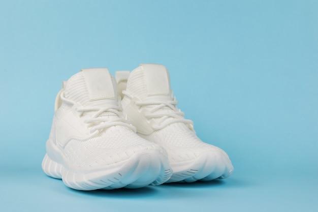 Witte modieuze fitness sneakers op een blauwe achtergrond. modieuze sportschoenen.