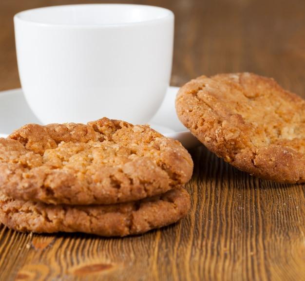 Witte mok en verse koekjes op een oude houten tafel