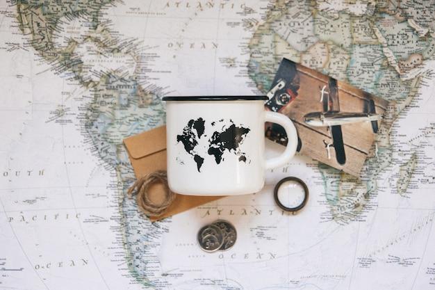 Witte mok met een wereldkaart op de achtergrond van de wereldkaart. bovenaanzicht.