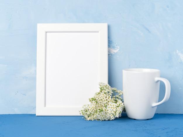 Witte mok met thee of koffie, frame, bloemboeket op blauwe tafel tegenover blauwe muur.