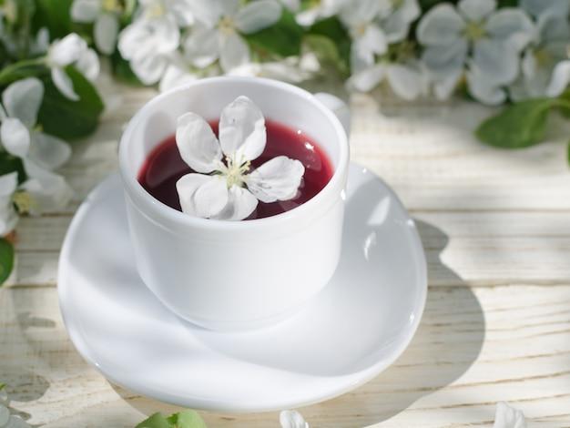 Witte mok thee op een houten tafel, appelbloesems op de achtergrond