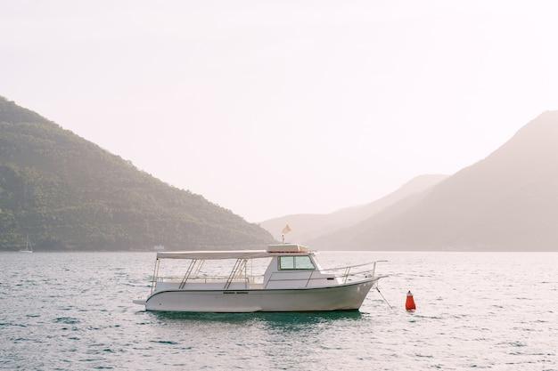 Witte motorboot met zonneluifel en kuip midden in de baai van kotor