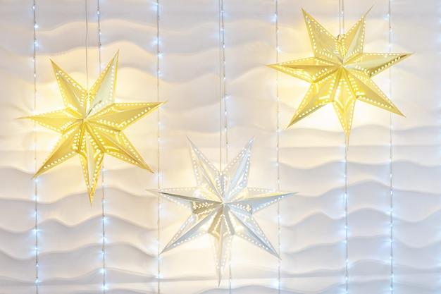 Witte muur kerstmis achtergrond met glanzende lichten. muur met een slinger.