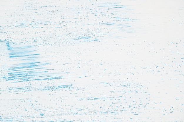 Witte muur met blauwe verf