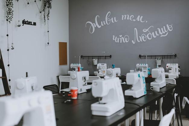 Witte naaimachines op tafel. een rij naaimachines, een werkplaats voor kleermakers.
