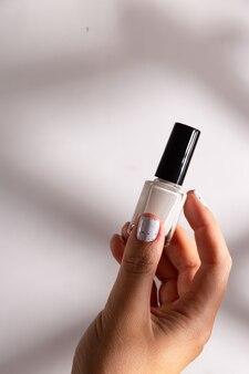 Witte nagellak in een fles en op de manicure van een vrouw