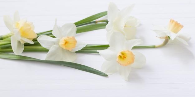 Witte narcissen op witte houten achtergrond